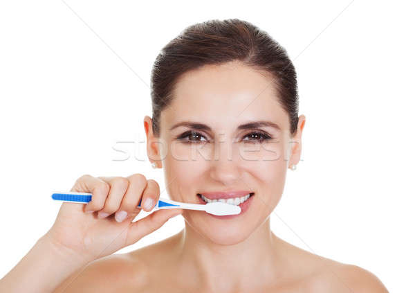 Smiling woman cleaning her teeth Stock photo © AndreyPopov