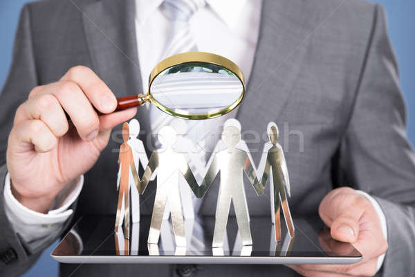 Holding magnifying glass and paper people Stock photo © AndreyPopov