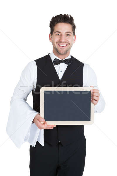 Smiling Young Butler Holding Blank Slate Stock photo © AndreyPopov
