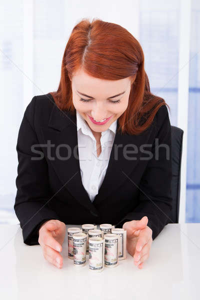 Businesswoman Protecting Rolled Dollar Bills Stock photo © AndreyPopov