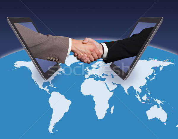 Business Handshake Emerging From Digital Tablets On World Map Stock photo © AndreyPopov