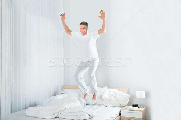 Mature Man Jumping On Bed Stock photo © AndreyPopov