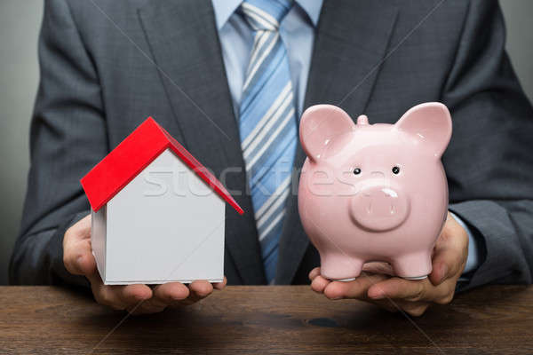 Stock photo: Businessperson With Piggy Bank And House Model