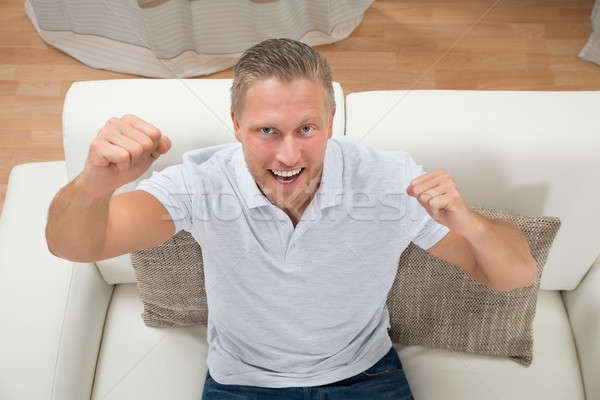 Man Clenching Fist On Sofa Stock photo © AndreyPopov