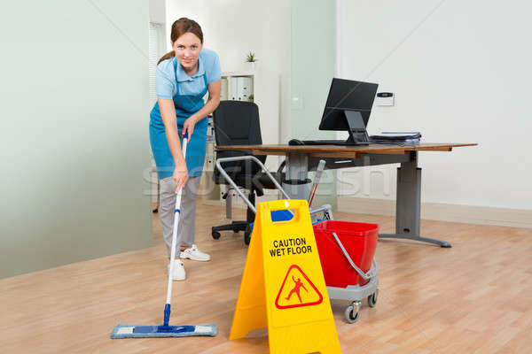 Female Janitor Cleaning Hardwood Floor In Office Stock photo © AndreyPopov