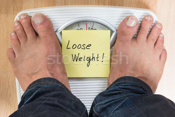 Man Standing On Weight Scale Stock photo © AndreyPopov
