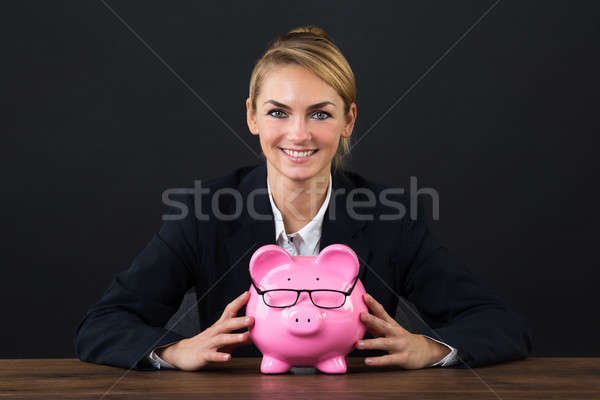Smiling Businesswoman With Piggybank On Desk Stock photo © AndreyPopov