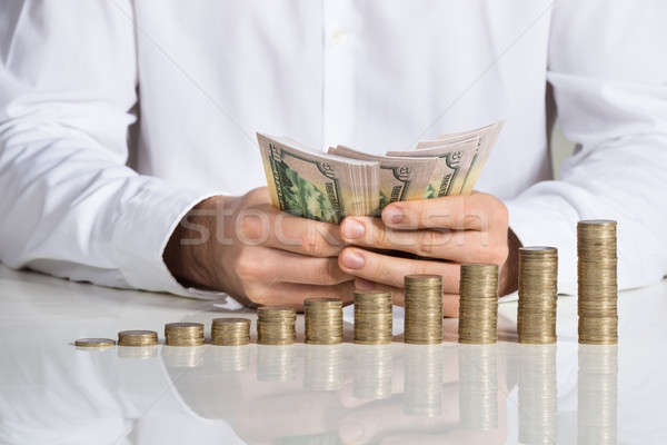 Businessman Counting Money At Desk Stock photo © AndreyPopov