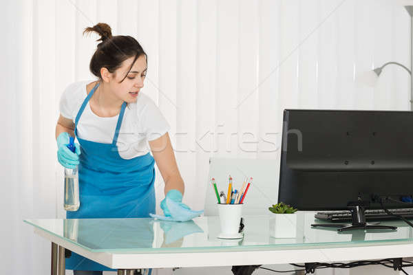 Young Female Janitor Cleaning Desk With Rag Stock photo © AndreyPopov