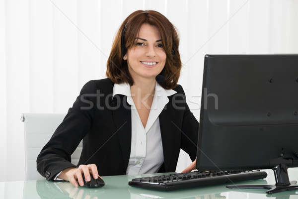Businesswoman With Headset Working On Computer Stock photo © AndreyPopov