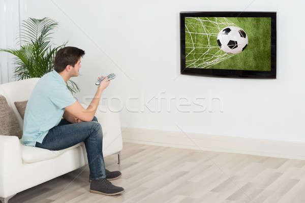 Férfi néz futball gyufa televízió fiatalember Stock fotó © AndreyPopov