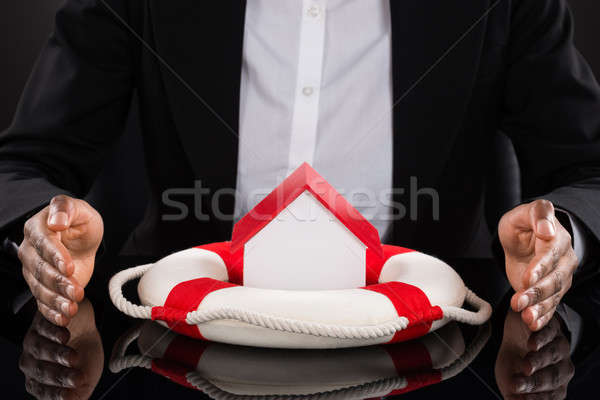 Businessperson's Hand Protecting House With Lifebelt Stock photo © AndreyPopov