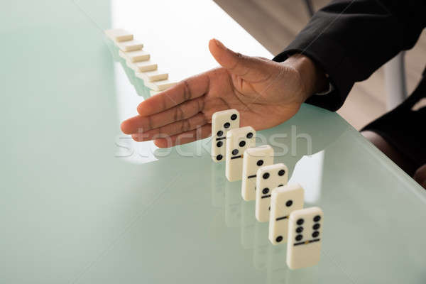 Businesswoman Hand Stopping Dominoes From Falling Stock photo © AndreyPopov
