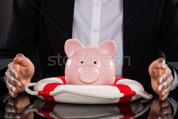 Businessperson Hand Protecting Piggybank With Lifebelt Stock photo © AndreyPopov