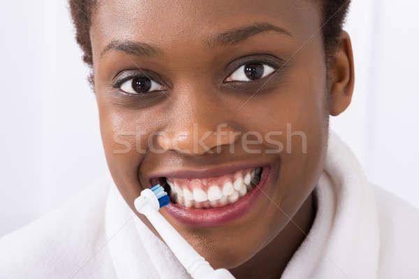 Afrikai nő fogmosás közelkép elektromos fogkefe Stock fotó © AndreyPopov
