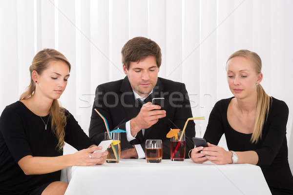 Friends Using Mobile Phones In Restaurant Stock photo © AndreyPopov
