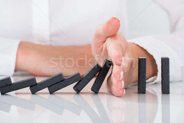 Person's Hand Stopping Dominos Falling On Desk Stock photo © AndreyPopov