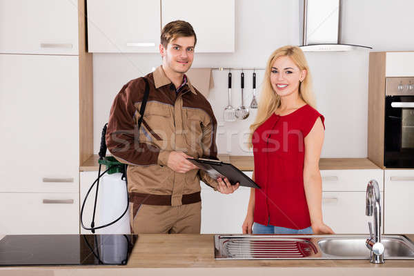 Woman Signing Document In Front Of Male Exterminator Stock photo © AndreyPopov