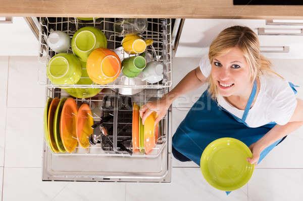 Genç kadın plakalar bulaşık makinesi görmek ev Stok fotoğraf © AndreyPopov