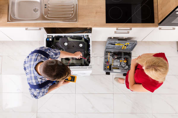 High Angle View Of Male Worker Repairing Washer In Kitchen Stock photo © AndreyPopov