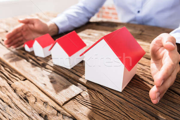 Businessman Protecting The House Models With Hands Stock photo © AndreyPopov