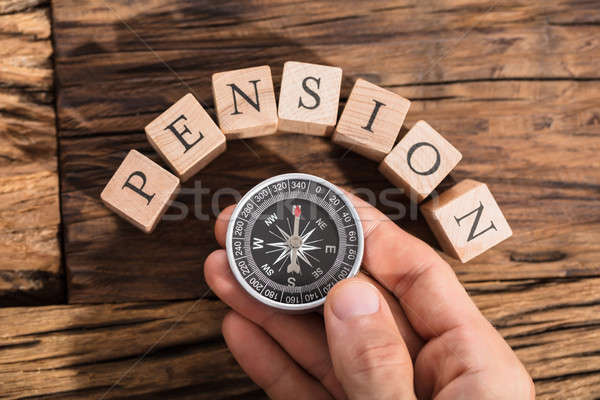 Hand Holding Compass On Pension Block Stock photo © AndreyPopov