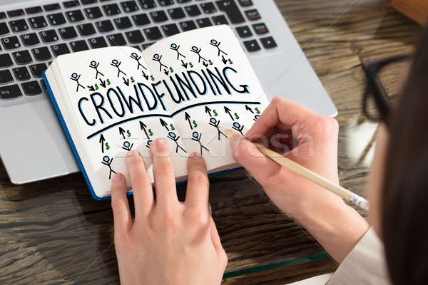 Business Person Drawing Crowdfunding Chart On Notebook Stock photo © AndreyPopov
