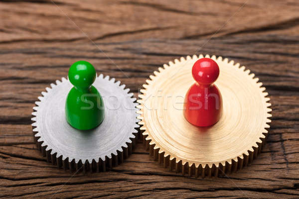 Red And Green Pawn Figurines On Interlocked Cogwheels Stock photo © AndreyPopov