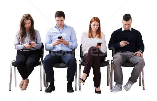 Stock photo: Business People Sitting On Chair Using Cell Phones
