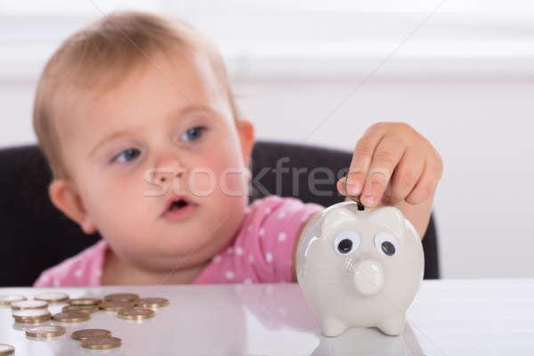 Baby Inserting Coin In Piggybank Stock photo © AndreyPopov