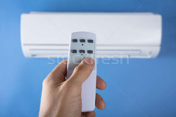 Hand Adjusting Temperature Of Air Conditioner Stock photo © AndreyPopov