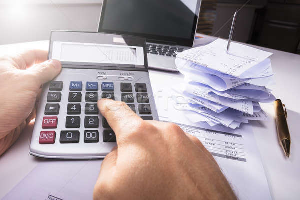 Person's Hand Calculating Invoice Near Bills And Laptop Stock photo © AndreyPopov