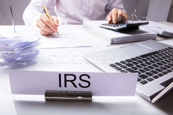 IRS Nameplate In Front Of Accountant Calculating Tax Stock photo © AndreyPopov