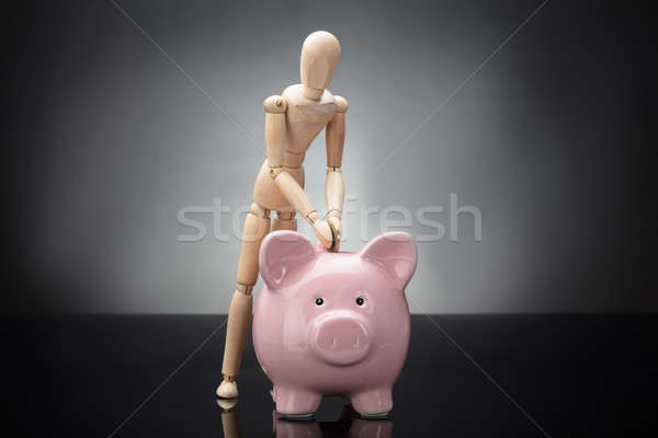 Wooden Dummy Inserting Coin In Piggy Bank Stock photo © AndreyPopov