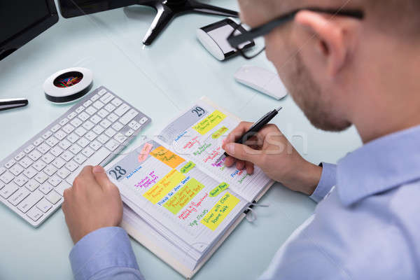 Stock photo: Businessman Writing Schedule In Diary