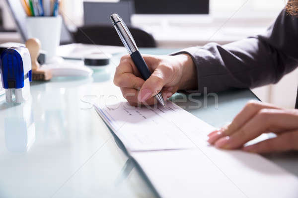 Businessperson Signing Cheque In Office Stock photo © AndreyPopov