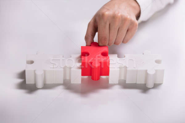 Person Placing Red Piece Between White Jigsaw Puzzles Stock photo © AndreyPopov