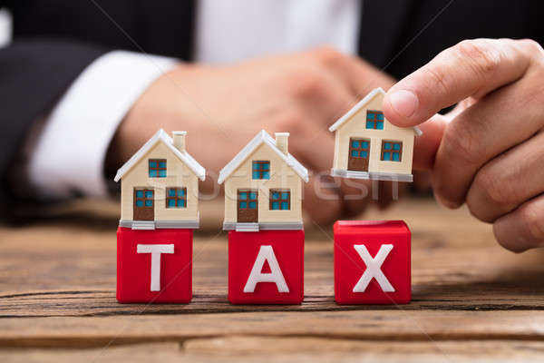 Businessperson placing house model over tax word blocks Stock photo © AndreyPopov