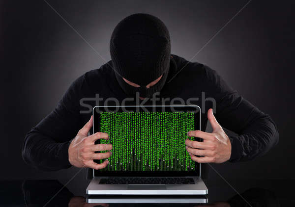 Hacker stealing data of a laptop computer Stock photo © AndreyPopov