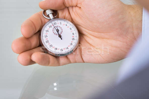 Business advisor holding stopwatch Stock photo © AndreyPopov