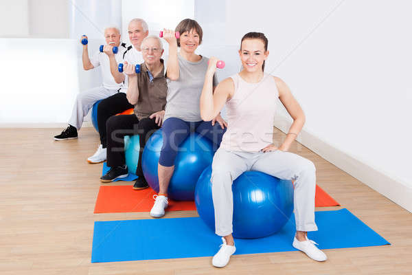 Stock photo: People Using Hand Weights While Sitting On Fitness Balls