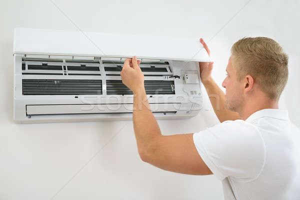 Man Adjusting Air Conditioning System Stock photo © AndreyPopov