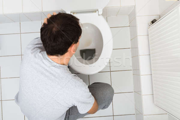 Man Vomiting In Bathroom Stock photo © AndreyPopov