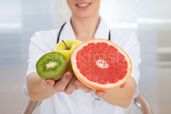 Dietician Holding Fresh Sliced Fruits Stock photo © AndreyPopov