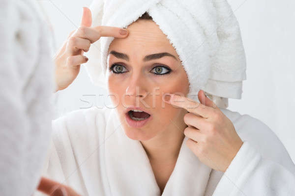 Worried Woman Looking At Pimple On Face Stock photo © AndreyPopov