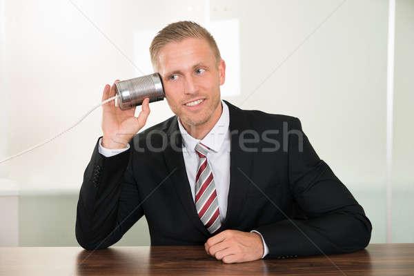 Işadamı dinleme kalay telefon genç büro Stok fotoğraf © AndreyPopov