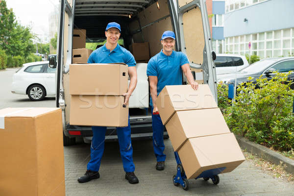Two Workers Loading Cardboard Boxes In Truck Stock photo © AndreyPopov