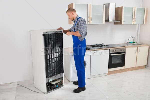 Szerelő javít hűtőszekrény fiatal átfogó konyha Stock fotó © AndreyPopov