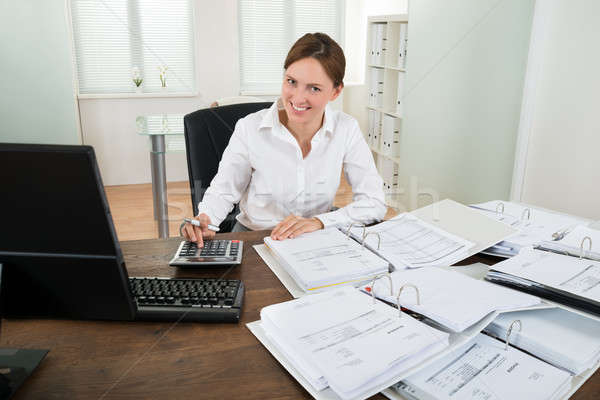Businesswoman Calculating Financial Data At Desk Stock photo © AndreyPopov
