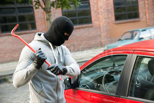 Thief Trying To Smash The Window Of The Car Stock photo © AndreyPopov